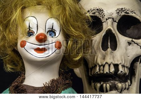 antique porcelain clown doll with scary skull looking over its shoulder