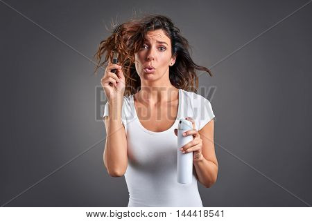 A beautiful young woman feeling sad while brushing her hair and holding a hairspray.