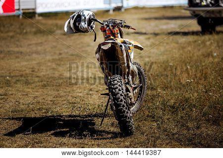 rear view of a racing motorcycle sports helmet hanging on handlebars