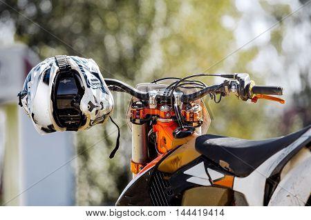 closeup sports helmet hanging on handlebars of a racing motorcycle