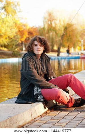 Young man autumn outdoor portrait sitting against autumn lake in park, long curly hairstyle