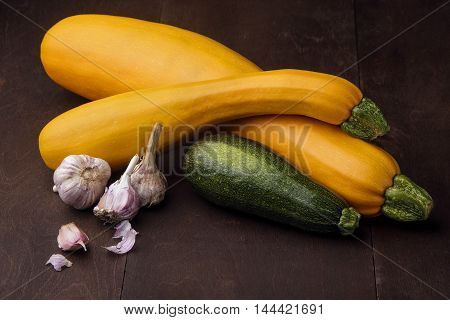Two yellow big and medium and small green zucchini on wooden table.And garlic, chiveFamily of zuccini.