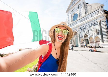 Young female traveler in blue dress and hat taking selfie photo with italian flag in front of Santa Maria Novella church in Florence.