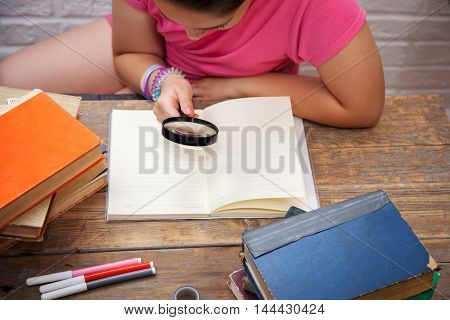 Girl sees through a magnifying glass in a notebook