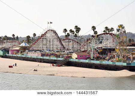 Santa Cruz, California, August 22, 2016 - a far off view of the ocean, beach, boardwalk, and rides at Santa Cruz Beach Boardwalk Amusement Park, mid-afternoon