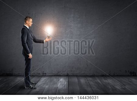 Side view of a businessman standing and holding glowing light bulb in his hand. Concepts and ideas. Business staff. Speculating and analyzing. Brainstorming.