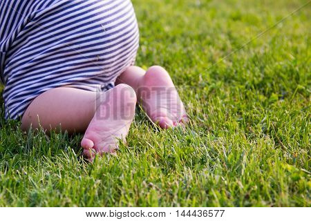Child Feet Barefoot on Green Grass. Healthy Lifestyle. Spring Time. Rear view. the concept of flatfoot the child is learning to crawl Close up.