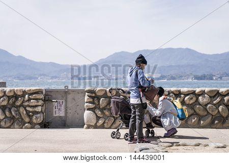 Miyajima, Japan - March 16, 2016: Miyajima on March 16, 2016. A Family with small child traveling in Miyajima beach.