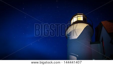 Lighthouse Beacon On A Starry Night. The Point Betsie Lighthouse beacon against a starry sky background. In panoramic orientation with copy space.