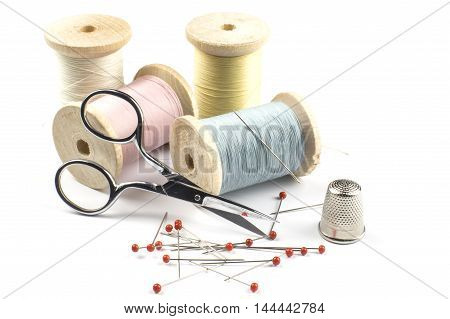 Sewing thread, scissors and Pins on white