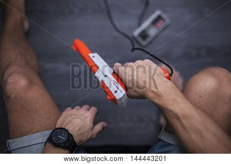 Gothenburg, Sweden - January 31, 2015: A shot from above of a young man's hands using a 1985 Nintendo Zapper, a remote game controller for the Nintendo Entertainment System developed by Nintendo Co., Ltd. in the 1980s. Natural lighting. Shot on a grey woo