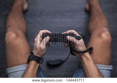 Gothenburg, Sweden - January 31, 2015: A young man's hands using a black Wii remote with Nunchuck, a game pad controller for the Nintendo Wii video game console developed by Nintendo Co., Ltd.