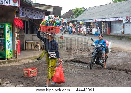Bali Indonesia -- February 28 2016 -- Woman carries basket on head through outdoor market in Bali Indonesia. Editorial Use Only.