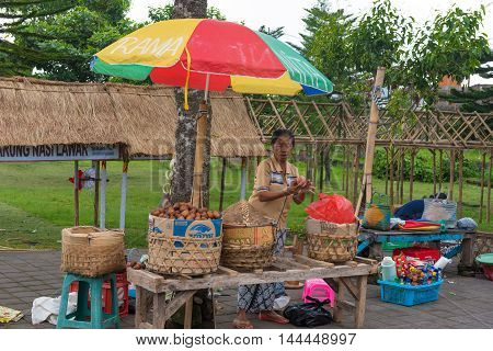 Bali Indonesia -- February 28 2016--Woman examines produce at a food stand. Editorial Use Only.