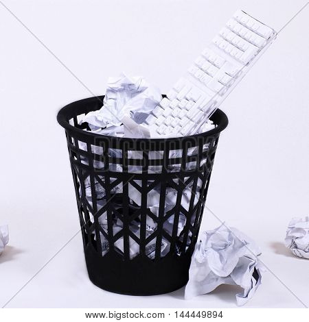 full wastepaper with crumpled papers and keyboard on white background, square toned image
