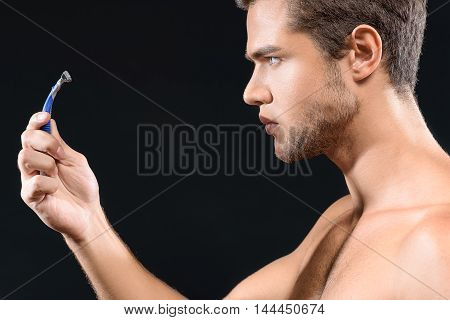 Pensive young man is making decision about shaving. He is holding razor and looking at it with hesitation. Isolated