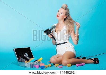 Full length young woman preparing to party sexy girl fashion model styling hair with curlers accessories and hairdreyer retro style vivid blue background