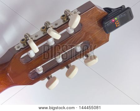 the guitar headstock backside with installed clip-on tuner that shows the note e