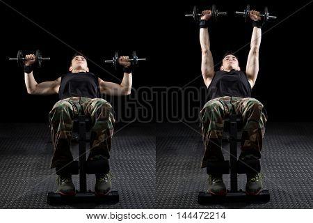 Inclined dumbbell chest press exercise. Studio shot over black.