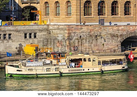 Basel, Switzerland - 27 August, 2016: a boat at pier on the Rhine river. The Rhine is a European river that begins in the Switzerland and empties into the North Sea in the Netherlands.