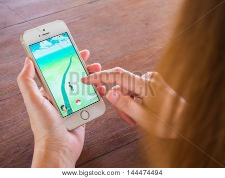 CHIANGRAI THAILAND - August 17 2016: Person holding mobile phone and playing Pokemon Go game application. Pokemon Go is a location-based augmented reality mobile game.