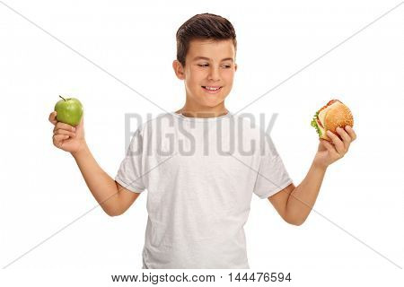 Indecisive kid holding an apple and a sandwich isolated on white background