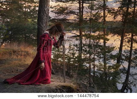 A young woman in medieval clothes with a sword praying outdoors