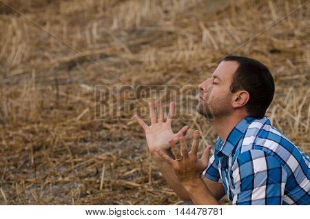 Young man in a plaid shirt lifting his hands in worship/praise in an outdoor field.