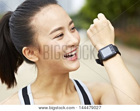 young asian woman jogger answering or making a call using a wrist watch wearable device.