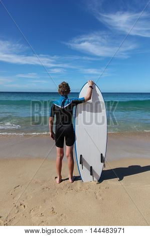 A boy looking out to the waves before going for a surf at Zenith Beach - Nelson Bay NSW Australia