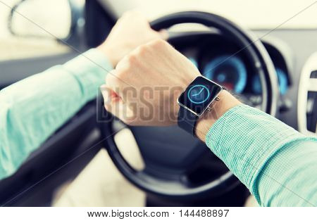 transport, business trip, technology, time and people concept - close up of man with wristwatch or smart watch driving car