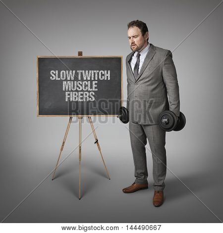 Slow twitch muscle fibers text on blackboard with businesssman holding weights
