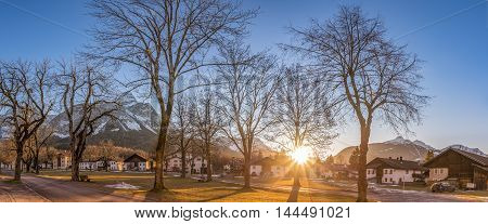 Alpine village under sun rays - Rural scenery with a mountain village under a clear sky and powerful sun. Picture taken in Ehrwald district of Reutte state of Tyrol Austria during winter.