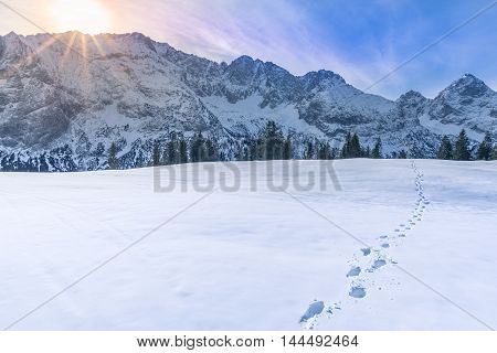 Mountain peaks in winter - Sunny alpine landscape with the peaks of the Austrian Alps mountains on the horizon and a thick blanket of snow in the foreground with footprints on it.