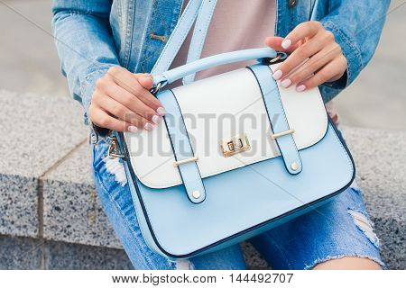 Fashionable young girl in a denim suit with a blue bag . Her pink manicure .Fashion and beauty