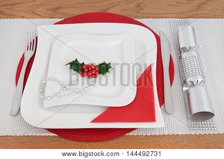 Christmas dinner table setting with white porcelain plates, holly, cutlery, serviette, silver bead strand and cracker with diamond decoration over oak background.