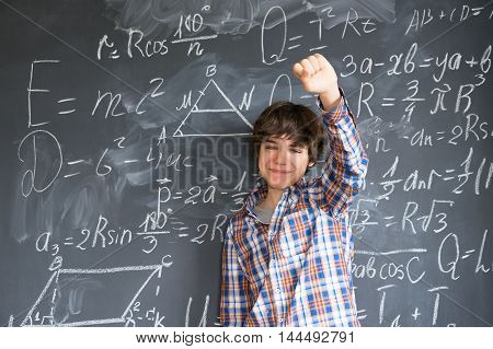 Teenage Boy finding idea with complicated math formulas on black board