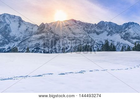 Sun shining over mountain peaks and snow - Lovely winter scenery with the Austrian Alps mountains covered in snow the trees line and a route from footsteps in the snow.