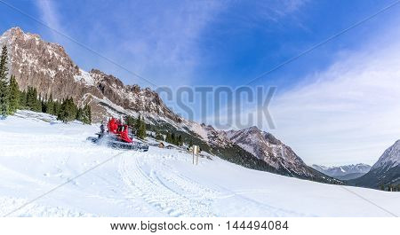 Winter on the Austrian mountain peaks - A sunny day of winter on the snowy pastures and the rocky peaks of the Austrian Alps mountains with the roads being cleared by a snow groomer vehicle.