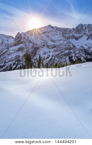 Winter sun over snowy mountain peaks - A lovely winter day in the Austrian Alps mountains from the Ehrwald municipality with the rocky peaks and snowy pastures warmed up by a bright and colorful sun.