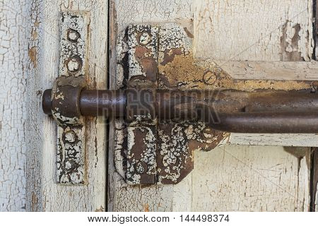 Locked: Very old deteriorating gate latch bolt in a locked position complete with rusting parts and peeling white paint on the wooden door.
