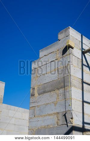 Builder's plumb line hanging against exterior corner wall of house build in progress.