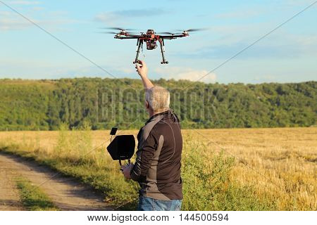 Silhouette Of A Man Operating A Drone With Remote Control For Video Shooting In A Summer Day