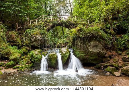 deep in the forest there is a small waterfall in switzerland in Luxembourg