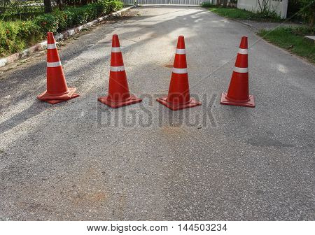 Traffic cone. Row of traffic cones white and orange stripes on gray asphalt copy space.