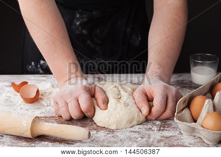Baker in black apron knead homemade dough on a wooden table for bread, pasta or pizza with eggs and milk.