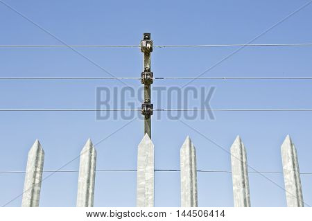 Steel fence holding a high voltage security wires against a blue sky
