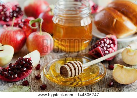 Honey, apple, pomegranate and hala table set with traditional food for Jewish New Year Holiday Rosh Hashana