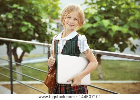 Cute schoolgirl with laptop on street
