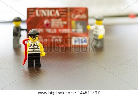 Orvieto, Italy - December 27th 2014: Lego mini figure thief on credit cards. Lego is a popular line of construction toys manufactured by the Lego Group